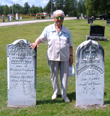 89 year old Lucy Jarratt stands next to the gravestones of her relatives, buried in Our Lady of Mount Carmel graveyard on the Howard Road, Blackville, NB. Summer 2006.